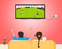Hållande ögonen på fotbollsmatch på TV Arkivfoto