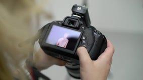 Hållande ögonen på foto för fotograf på kamera arkivfilmer