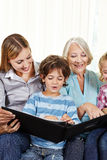 Hållande ögonen på fotoalbum för familj med barn Arkivfoton