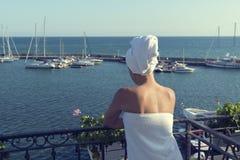 Hållande ögonen på havsfjärd för ung kvinna med yachten från balkongen arkivfoto