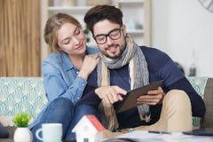 Hållande ögonen på internet för lyckliga unga par på deras minnestavla arkivfoto