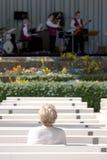 Hållande ögonen på Jazz för Lone gammalare kvinna royaltyfria foton