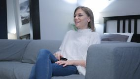 Hållande ögonen på komedi för lycklig kvinna på TV arkivfoto