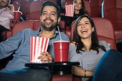 Hållande ögonen på komedi för par på teatern arkivbild