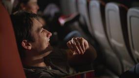 Hållande ögonen på komedifilm för ung man på bion Den manliga åskådaren tycker om komedifilmen stock video