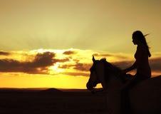hållande ögonen på kvinna för hästsilhouettesolnedgång Royaltyfria Bilder
