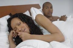 Hållande ögonen på kvinnagråt för man i säng Arkivfoton