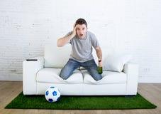 Hållande ögonen på lek för stressad fan för fotboll fanatisk på tv som är nervös i misstroframsida som, om katastrofen kommer Royaltyfri Foto