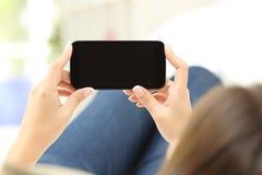 Hållande ögonen på massmedia för kvinna i en smart telefon royaltyfria bilder