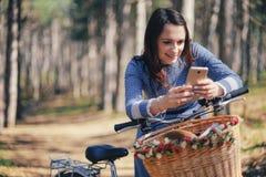 Hållande ögonen på massmedia för lycklig flicka i ett smart telefonsammanträde i gatan bredvid hennes cykel Royaltyfri Bild