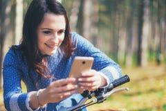 Hållande ögonen på massmedia för lycklig flicka i ett smart telefonsammanträde i gatan bredvid hennes cykel Arkivbilder
