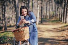 Hållande ögonen på massmedia för lycklig flicka i ett smart telefonsammanträde i gatan bredvid hennes cykel Arkivfoto
