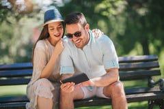 Hållande ögonen på massmedia för lyckliga par i en digital minnestavla royaltyfri bild