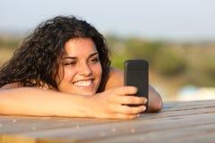 Hållande ögonen på massmedia för rolig flicka i smart telefon Royaltyfri Fotografi