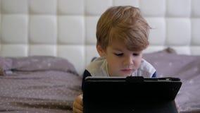 Hållande ögonen på minnestavla för pojke, medan ligga på säng stock video