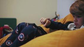 Hållande ögonen på minnestavla för pojke, medan sitta på en puff lager videofilmer