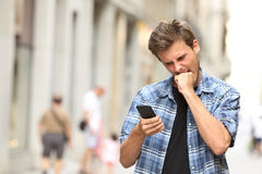 Hållande ögonen på mobiltelefon för rasande ilsken man Royaltyfri Foto
