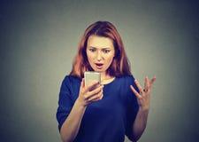 Hållande ögonen på nyheterna för chockad kvinna på smartphonen royaltyfri foto