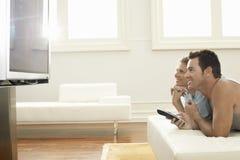 Hållande ögonen på plasmaTV för par hemma Royaltyfria Bilder