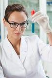 Hållande ögonen på provrör för kemist Royaltyfria Bilder