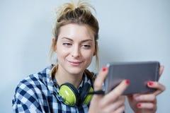 Hållande ögonen på serie för flicka på telefonskärmen royaltyfria foton