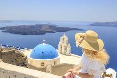 Hållande ögonen på sikt för blond kvinna av Santorini nära tre klockor av Fira royaltyfri foto