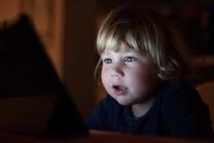Hållande ögonen på skärm för förvånad babyansikte på natten royaltyfri bild