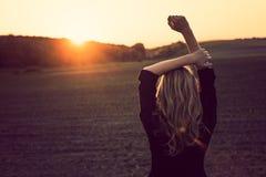 Hållande ögonen på solnedgång för blond kvinna Fotografering för Bildbyråer