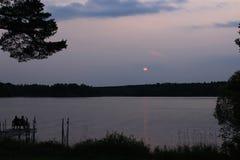 Hållande ögonen på solnedgång för folk över sjön Royaltyfri Bild
