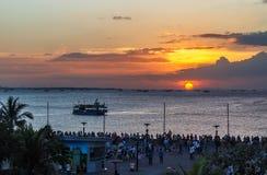 Hållande ögonen på solnedgång för folk på den Manila fjärden i Filippinerna arkivfoton