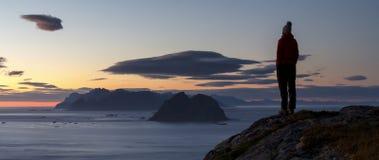 Hållande ögonen på solnedgång för fotvandrare ovanför de Lofoten öarna, Norge Royaltyfri Foto