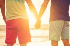 Hållande ögonen på solnedgång för glade par