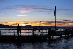 Hållande ögonen på solnedgång för konturpar på sjön Arkivfoto