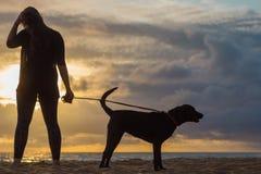 Hållande ögonen på solnedgång för kvinna med hunden Arkivbilder