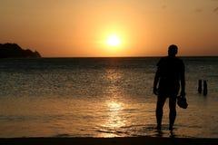 Hållande ögonen på solnedgång för man royaltyfri bild