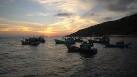 Hållande ögonen på solnedgång på stranden med vietnamesiska traditionella fiskebåtar som svävar på det sceniska blåa havet i bakg lager videofilmer