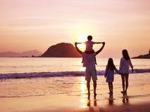 Hållande ögonen på soluppgång för asiatisk familj på stranden Arkivfoto