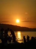 Hållande ögonen på soluppgång för folk över havet Arkivfoton