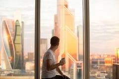 Hållande ögonen på soluppgång för man i fönster Fotografering för Bildbyråer