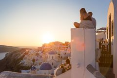 Hållande ögonen på soluppgång för par och ta semesterfoto på den Santorini ön, Grekland royaltyfria bilder
