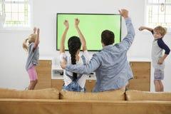 Hållande ögonen på sportar för familj på television och att hurra Arkivbild