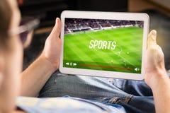 Hållande ögonen på sportar för man på minnestavlan Fotboll- och fotbolllek royaltyfria bilder
