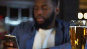 Hållande ögonen på sportlek för nervös man i baren som kontrollerar hans vad i mobil applikation lager videofilmer