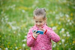Hållande ögonen på tecknad film för flicka och spelalekar på den smarta telefonen Arkivbild
