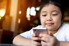 Hållande ögonen på tecknad film för liten flicka på mobila enheten Fotografering för Bildbyråer
