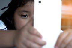 Hållande ögonen på tecknad film för liten flicka på mobila enheten Arkivbilder
