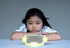 Hållande ögonen på tecknad film för liten flicka på mobila enheten Arkivfoto