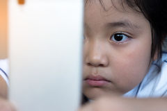 Hållande ögonen på tecknad film för liten flicka på mobila enheten Royaltyfri Bild