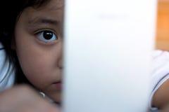 Hållande ögonen på tecknad film för liten flicka på mobila enheten Royaltyfria Foton
