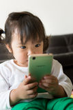 Hållande ögonen på tecknad film för liten flicka på mobila enheten Arkivbild